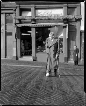 Henk Schijvenaar met voet in het gips voor zijn zaak in Amsterdam